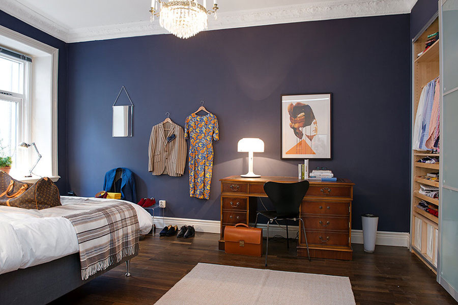 scandinavian style apartment with blue walls in bedroom