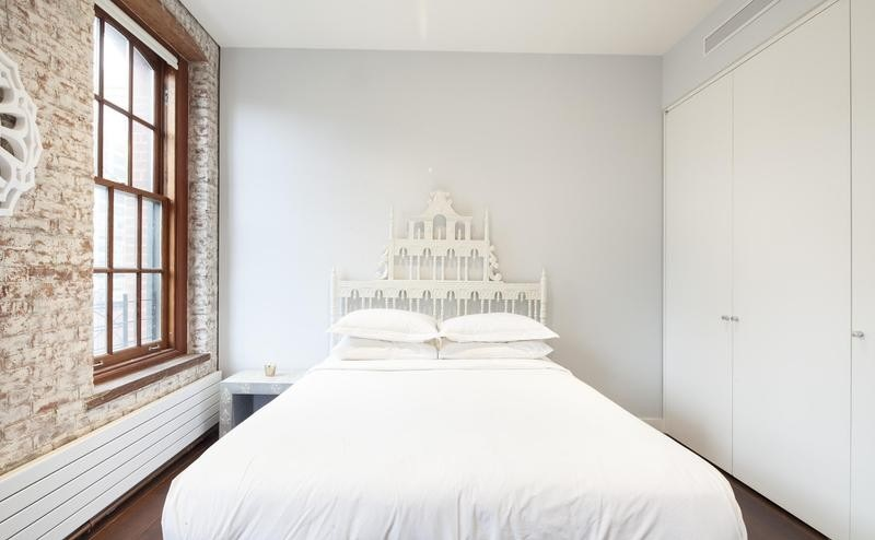 white bedroom with brick wall for apartment in NY