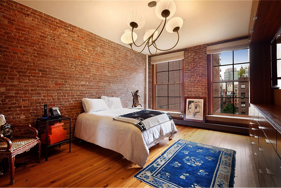 wide loft style apartment bedroom with red brick walls