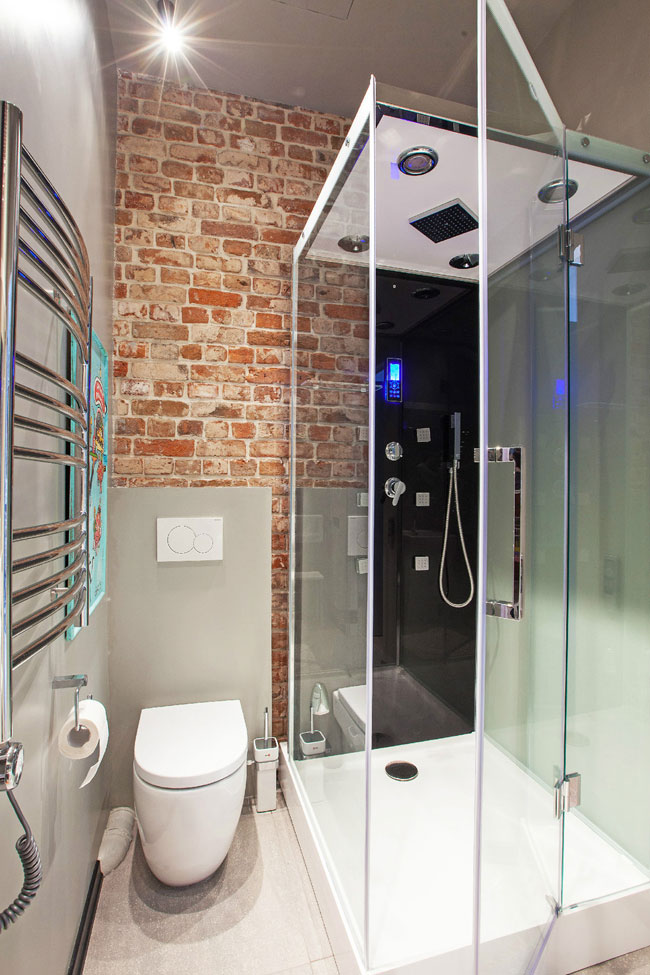 loft shower room with red brick wall
