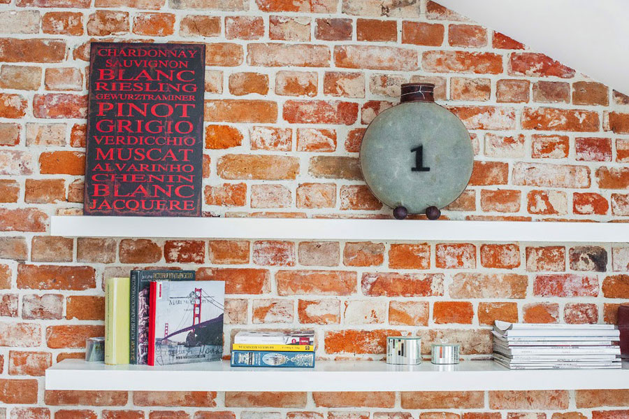 red brick wall with white wall shelfs from IKEA