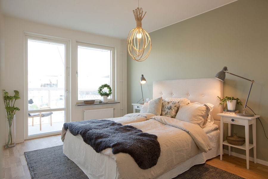 scandinavian apartment bedroom with olive green wall