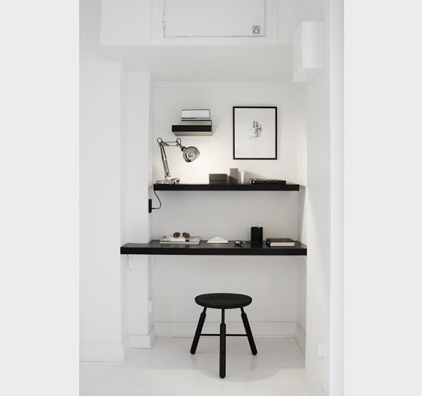 white home office with black wall shelves